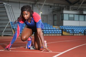 Image shows black woman in sports gear crouched down at starting line on race track - DM Orthotics case study
