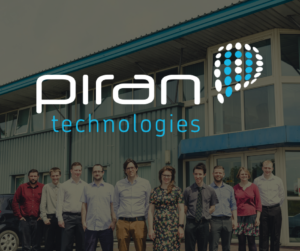 Image of the Piran Technology team standing outside their building. 8 men 2 women. Photo has the Piran Technology logo on top of it.