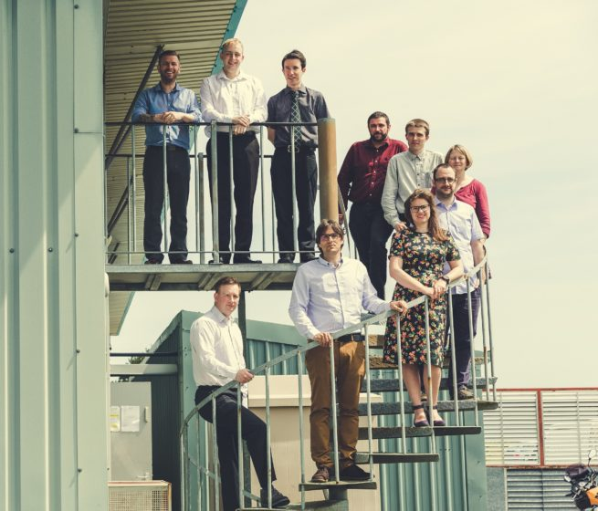 Image shows the piran technologies team standing on an outdoor spiral staircase
