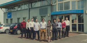 Image shows the piran technologies team standing in a V formation outside their office smiling at the cameras
