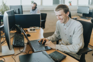 Piran Technologies male employee sat working at a laptop computer smiling