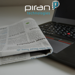 Image shows a newspaper and a laptop on a desk - covered with the Piran Technologies logo